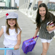Little student girls going to school in city - Stock Photo