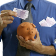 Businessman insert euro notes in piggy bank - Stock Photo