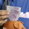 Businessman insert euro notes in piggy bank — Stock Photo