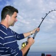 Stock Photo: Angler fishermfighting big fish rod and reel