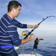 Angler fisherman fighting big fish rod and reel - Stok fotoğraf