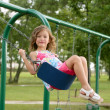 Beautiful little girl playing with swing — Stock Photo