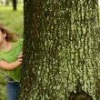 Stock Photo: Two twin little girls playing in tree trunk