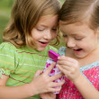 Two little twin sisters playing with pink box — Stock Photo #5500294