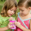 Stock Photo: Two little twin girls find a dollar note inside a box