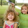 Two twin sisters pretending to be hairdresser — Stock Photo #5500303