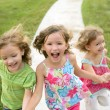 Three sister girls playing running on the park — Stock Photo