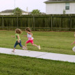 Three sister girls playing running on the park — Stock Photo #5500310