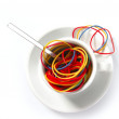Colorful rubber bands in breakfast cup — Stock Photo