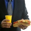 Businessman eating junk fast food — Stock Photo