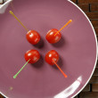 Tomatoes snack in a purple dish and colored sticks — Stock Photo