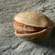 One pistachio over wooden gray background - Stock Photo