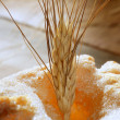 Delicious roll bakery sugar and wheat spikes — Stock Photo