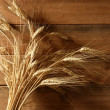 Royalty-Free Stock Photo: Ear golden wheat spike over wooden background