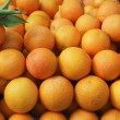 Valencia oranges stacked on market - Stock Photo