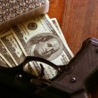 Dollar notes and gun, black pistol - Stock Photo