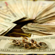 Dollar notes and gold rings over tablecloth - Stock Photo