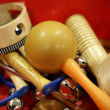 Mixed percussion toy instruments on red - Stock Photo