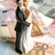 Wedding couple figurine over euro notes — Stock Photo