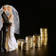 Wedding couple figurine and golden coins — Stock Photo
