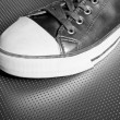 Silver sport shoe detail over gray steel - Stock Photo