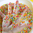 Children hand full of little colorful sweets - Stock Photo