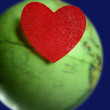 Candy valentines heart over the world green global earth map — Stock Photo