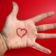 Red heart shape drawed on a male human hand — Stock Photo #5503737