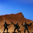 Plastic toy soldier over wooden mountain — Stock Photo