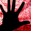 Royalty-Free Stock Photo: Backlight of human hand over red textured surface