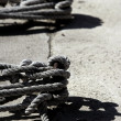 Boat bollard, ropes and knots in mediterranean harbor - Stock Photo