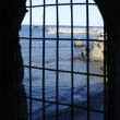 Blue sea behind the jail, arch window — Stock Photo