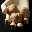 Mannequin wooden hand holding three walnuts — Stock Photo #5504108