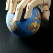 The world map in wood mannequin hand, black backgorund — Stock Photo
