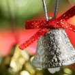 Silver bell in the christmas tree with red ribbon — Stock Photo