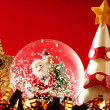 Santa claus figurine on a glass snowing ball - Stock Photo