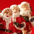 Three Santa Claus figurines over red background, studio — Stock Photo #5504154