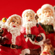 Three Santa Claus figurines over red background, studio — Stock Photo #5504155