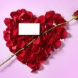 Cupid arrow in a red rose petals heart shape - Stock Photo