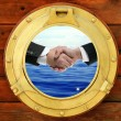 Businessmen handshake view from boat round window — Stock Photo