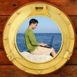 Businessman with computer, boat window view — Stock Photo