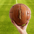 Aged vintage retro football leather ball - Stock Photo