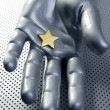 Golden star on silver futuristic hand — Stock Photo