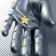 Golden star on silver futuristic hand — Stock Photo #5504473