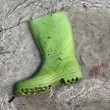 Royalty-Free Stock Photo: Green boots trash on beach shore pollution