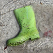 Green boots trash on beach shore pollution — Stock fotografie