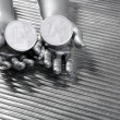 Two silver euro coins in futuristic robot hands - Stock Photo