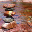 Stock Photo: Rolling stones stacked red rodeno limestone in river