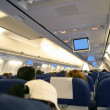 Airplane with passengers interior view - Stock Photo