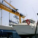 Dock crane elevating a fishing boat — Stock Photo #5505031